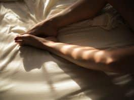 Woman in bed pleasuring herself